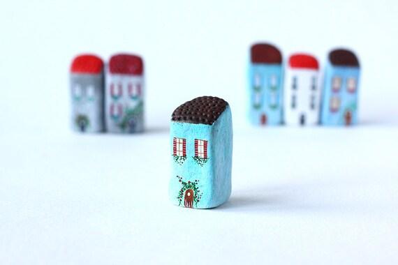 Petite maison de maison - bleue argile italienne avec toit brun, fleurs blanches et rouges et volets rouges