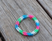 Thickly striped pink, green, blue and white/glow in the dark fishtail style, rubberband bracelet
