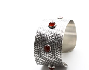 """Wide sterling silver cuff bracelet with a geometric surface pattern and a row of five crimson red carnelian stones - """"Llovera Cuff"""""""