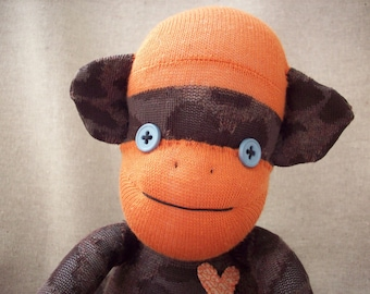 A sock monkey in brown leopard print with orange - Sam