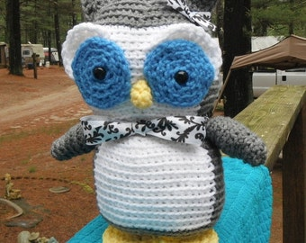 grey and white amigurumi owl with blue eyes and ribbbon accents