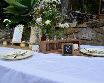 Rustic wedding table centerpiece. Vintage glass bottle stand made from recycled wood.
