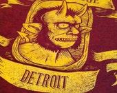 Le Nain Rouge Detroit T-Shirt Gold on Cranberry (Sizes: XS,S,M,L,XL,2XL)