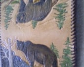 Hand tooled leather checkbook cover featuring a grizzly bear on each side