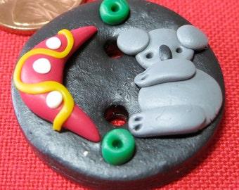 "Polymer ceramic molded button. Black base, gray  koala bear with red crescent shape and green cherrio shapes. 1""+ across.WCKG(mem)14.1-7.3"
