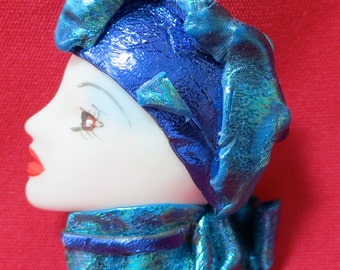 """Unusual brooch, striking pose of lady's head in profile set in lovely blue exotic head gear. 2.25"""" x 1.75"""" inches. VI14.3-27.11."""