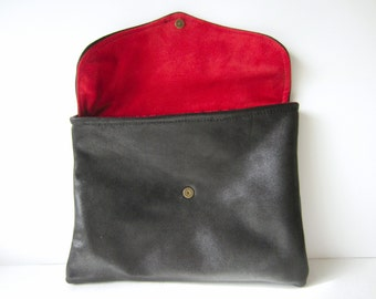 one-of-a-kind black leather clutch with red suede under flap and colorful interior