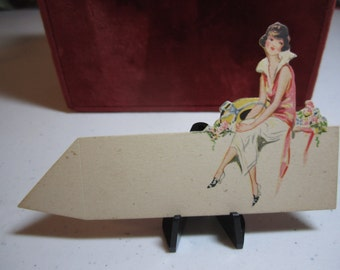 Unused 1920's die cut art deco place card fashionably dressed lady sitting next to flowers and holding a hat