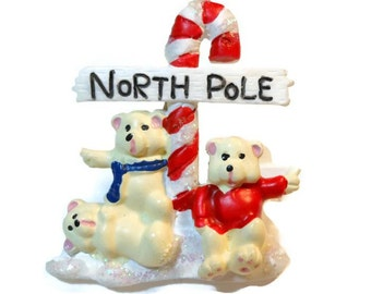 Christmas brooch - which way to the North Pole now? Three bears hitchhiking their way to the North Pole in front  of a candy cane road sign