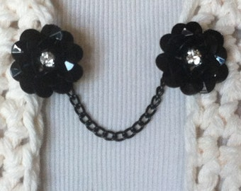The mattie black rose with rhinestone sweater clip adds a subtle touch of romance to any outfit.