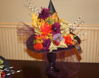 Paper mache witch hat decorated with artificial fall flowers and plum tulle accented with twigs painted and black and white. halloween deco