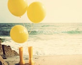 Yellow balloons and rain boots on the beach