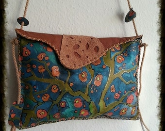 A painted handmade leather purse/bag with painted blossomed tree