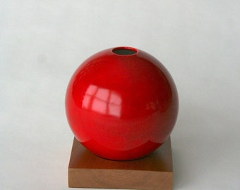 red ceramic vase with solid cherry base