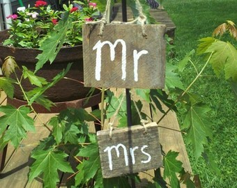 handmade weathered barnwood wedding signs MR and Mrs tied with a jute twine hang on the bride and grooms chair or use as photo props