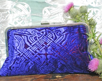 A strong blue kisslock clutch bag in an embossed iridescent velvet celtic design