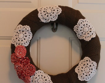 Brown burlap wreath with fabric flowers and doilies