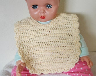 Baby bib is hand made using a crochet stitch with a light yellow cotton yarn with a white opal essence button closure;great baby shower gift
