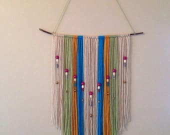 Wall hanging, with varying colored yarn, and beading. Measures 37in x 18in.