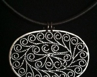 Gold filigree pendant on cotton necklace base