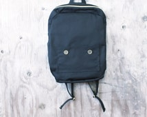 black backpack, simple medium sized backpack with brass zipper and buttons