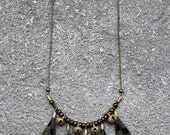 Cut 5, necklace, feathers and golden bells