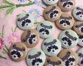 Cross-stitch Nigel the raccoon button badge