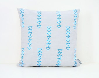 Light grey linen pillow cover with geometric tribal design in turquoise.