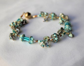 Hand Beaded Charm Bracelet with Freshwater Keishi pearls for charms. Teal, bronze, blue green