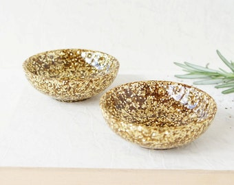 Pair of two small resin salt and pepper spice pinch trinket dish bowls in gold glitter sparkle.