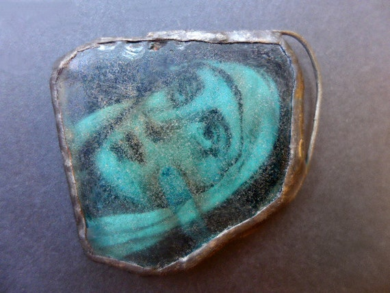 Saintly. Beach glass charm with solder and ephemera.