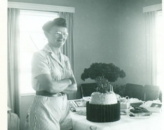 1953 A Happy Mother Standing Next To Flower Bouquet on Kitchen Table Arms Crossed Smile Vintage Photo Black and White Photograph