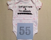 DISCOUNTED --  Good but Not Perfect -- #55, see photos -- I just got here & I'm already awesome  --- pink bodysuit size 0-3 months