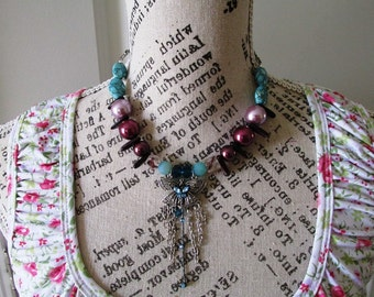 Beaded Statement necklace made with lavender,  purple, and turquoise  beads and a silver butterfly focal