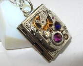 Steampunk  necklace book locket  with vintage watch  movement and purple and royal blue Swarovski crystals