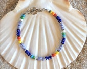 """This colorful bracelet is made with African """"Christmas"""" trade beads and  sterling silver components. It measures 7 1/4 inches."""