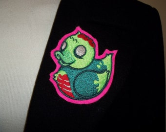 Zombie rubber ducky embroidered on bright pink felt with brooch fastening on the back, measuring 3.5in x  3in.