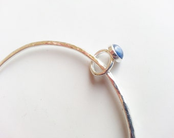 Silver bangle, hammered with minature ring and sodalite cabachon
