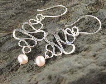 Sterling silver earrings with pink pearls.