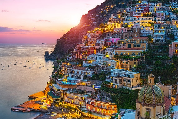 Walk along the Jeweled Coast of Positano, Italy at Sunset to get the real experience of the glittering city. Positano is the coast's most picturesque and photogenic town, with steeply-stacked houses tumbling down to the sea in a cascade of sun-bleached peach, pink and terracotta colors. No less colorful are its steep streets and steps lined with wisteria-draped hotels, smart restaurants and fashionable boutiques.