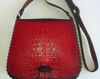 Gaucho bag with red crocodile print.
