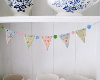 Eat More Cake - mini ceramic bunting with buttons. Made in Wales, UK. Pastel pink, blue, green