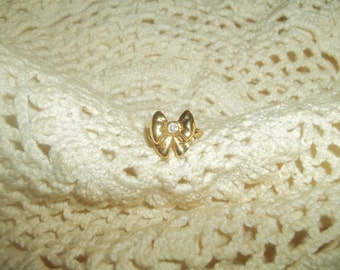 Avon Signed Golden Bow Ring With A Small Clear Cubic Zirconia Stone