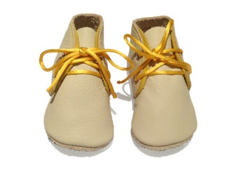 Handmade leather lambswool lined baby shoes.  Cream and yellow soled soled leather crib shoes.