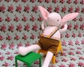White Woollen Bunny - Handmade plush sculpture wearing green felt shorts.