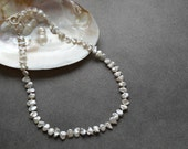 White Lustrous Keshi Pearl Necklace Hand Tied with Silk Cord and has a Sterling Silver Toggle Clasp