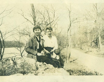 1918 Friends Women Sitting on Rocks Outside Winter Holding Fancy Hats Antique Vintage Black White Photo Photograph