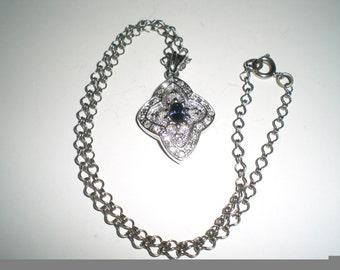 Silvertone Metal Pendant with Clear Rhinestones Circling and a Blue Rhinestone in the Center