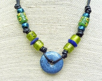 Slate Blue Donut Necklace - Blue Ceramic Focal, Olive Green Pony Beads, Green Recycled Glass Krobo Beads, Black Leather Necklace