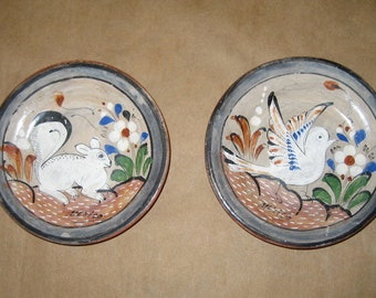 pair of vintage ceramic Mexican clay wall hangings with bird  and squirrel designs
